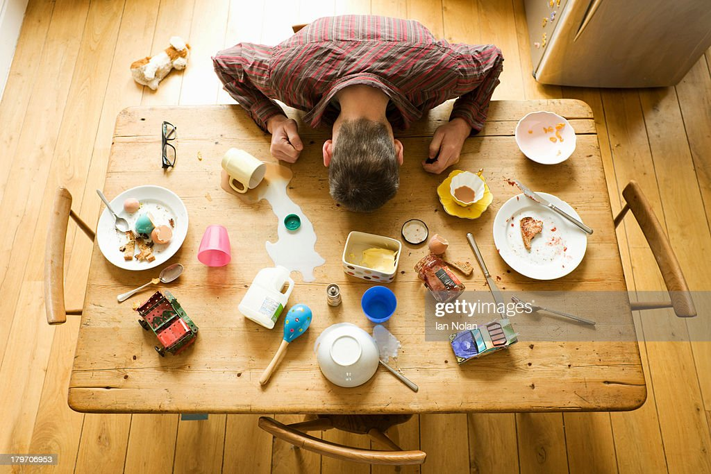 Overhead view of breakfast table with mature man amongst messy plates