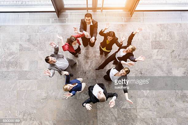 Overhead view of business team in circle jumping for joy