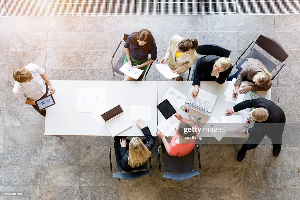 Overhead view of business team meeting at desk in office
