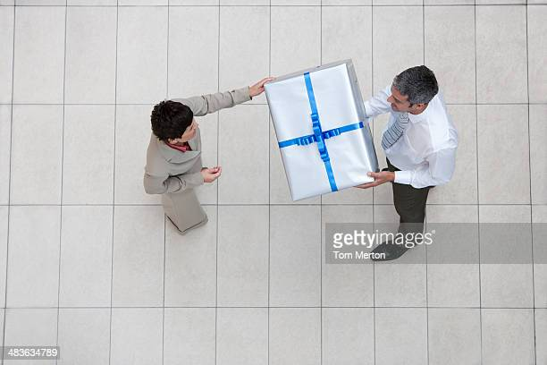 Overhead view of businessman and woman with gift box