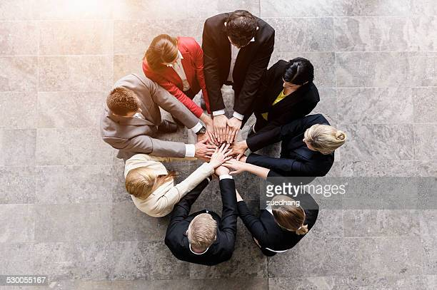 Overhead view of businessmen and women in circle with hands together
