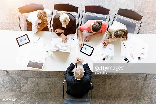 Overhead view of businessmen and women meeting client at desk in office