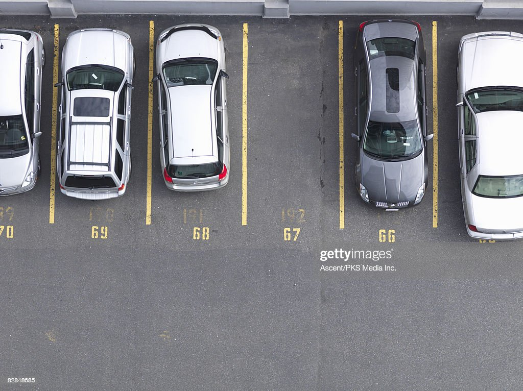 Overhead view of cars in parking lot, one empty  : Stock Photo