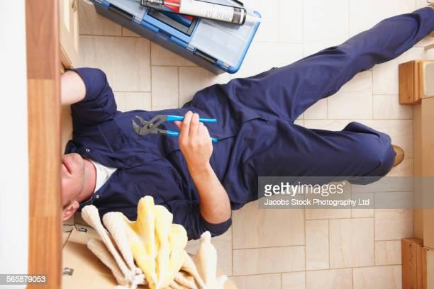 Overhead view of Caucasian plumber repairing sink