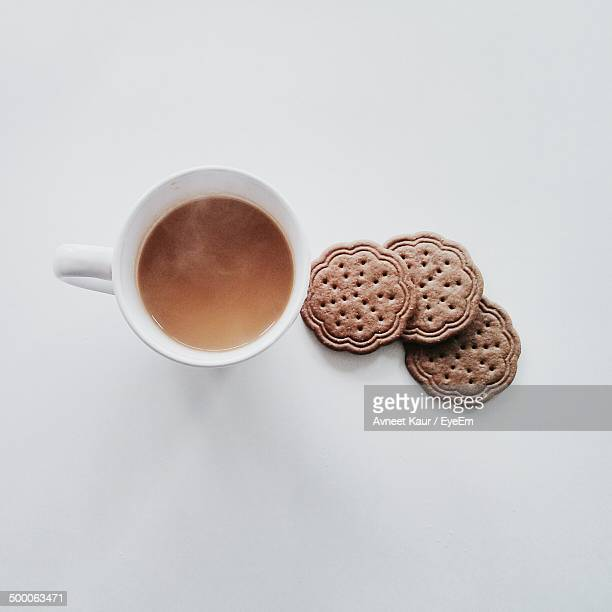 Overhead view of coffee with biscuits against white background