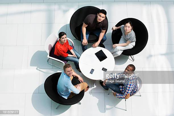 Overhead view of colleagues in meeting, looking up at camera