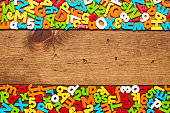 Overhead view of multi colored alphabets and numbers arranged in frame on wooden background. Flat lay of colorful letter magnets on borders of wood. Empty space can be used for advertisement purpose.
