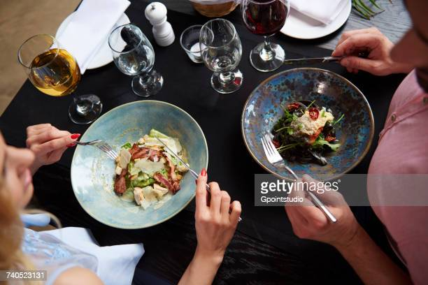 Overhead view of couple eating lunch at restaurant table