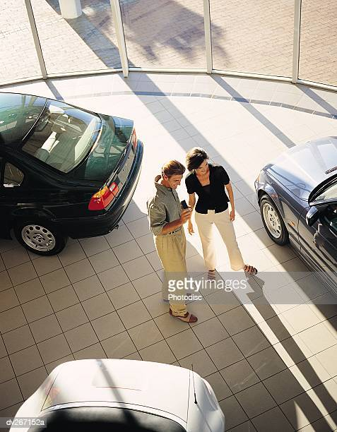 Overhead view of couple looking at cars in showroom