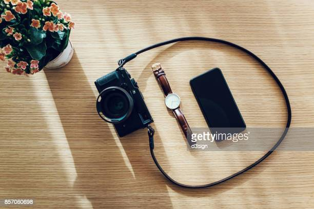 Overhead view of daily essentials, including flat lay camera, watch and smartphone