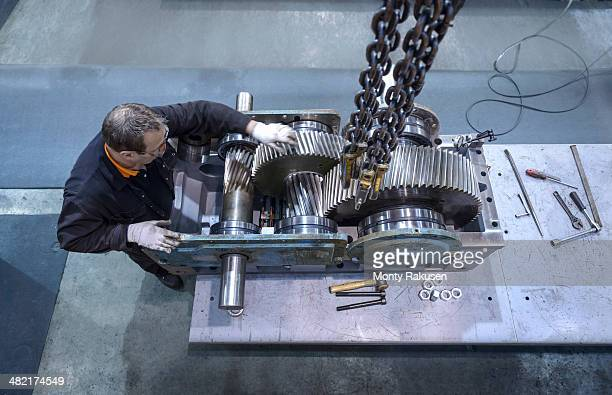 Overhead view of engineer repairing industrial gearbox in factory