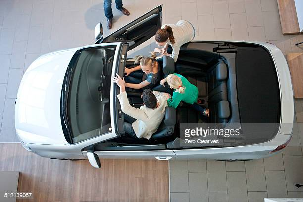 Overhead view of family trying out convertible car in car dealership