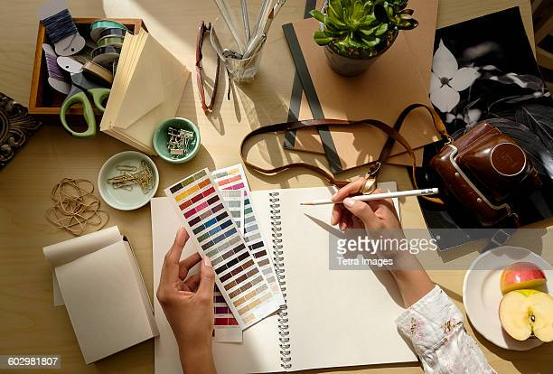 Overhead view of female hands writing in note pad