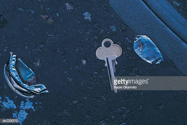 Overhead view of flattened bottle top and metal key on shiny black asphalt