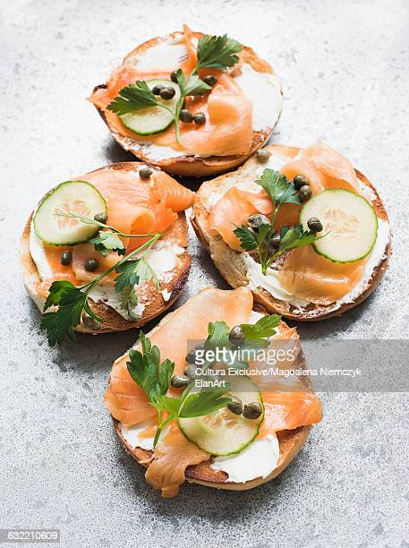 Overhead view of four smoked salmon and cream cheese bagels