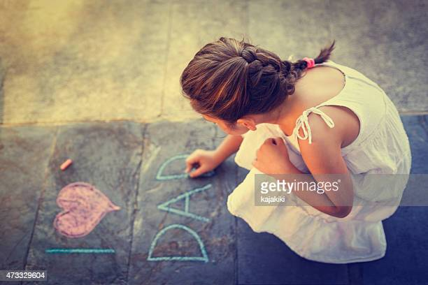 Overhead view of girl writing on the sidewalk