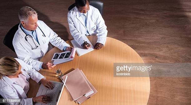 Overhead View Of Healthcare Team Discussing Cases