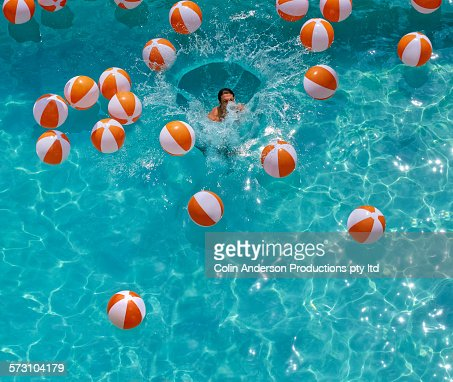 Overhead view of Hispanic man jumping in swimming pool