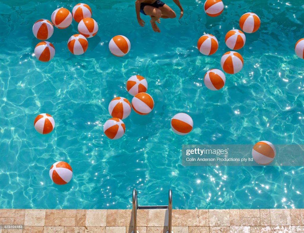 Overhead view of Hispanic man jumping in swimming pool