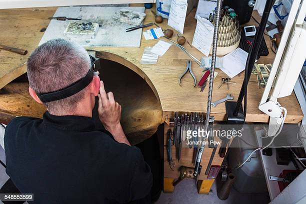 Overhead view of jewellery craftsman at workbench
