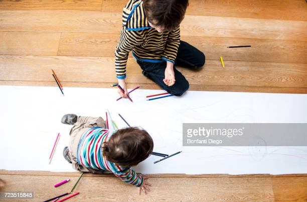 Overhead view of male toddler and big brother sitting on floor drawing on long paper
