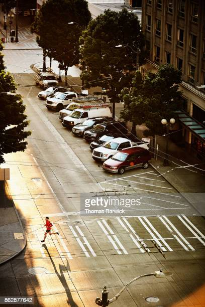 Overhead view of man running across crosswalk on city street during early morning run