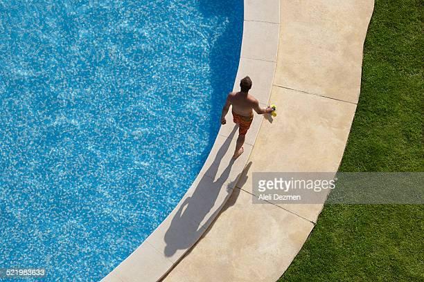 Overhead view of man walking around swimming pool