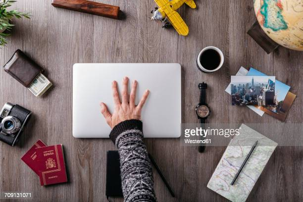Overhead view of mans hand and travel items on table