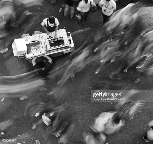 Overhead view of men at outdoor food stall with blurred people around