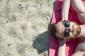 Overhead view of mid adult man in sunglasses sunbathing on sand