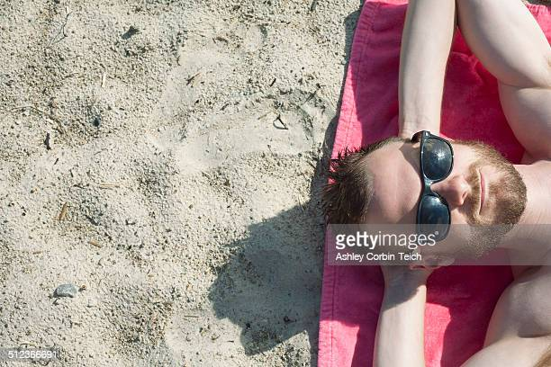 Overhead view of mid adult man in sunglasses sunbathing on sand