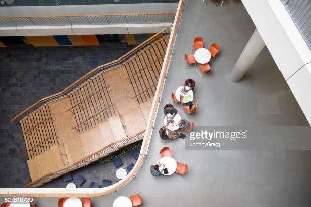 Overhead view of modern open plan college interior with tables and staircase