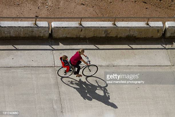 Overhead view of mother and son sharing bicycle