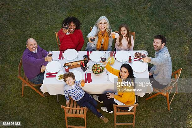 Overhead view of multi generation family dining outdoors looking up at camera, making a toast smiling