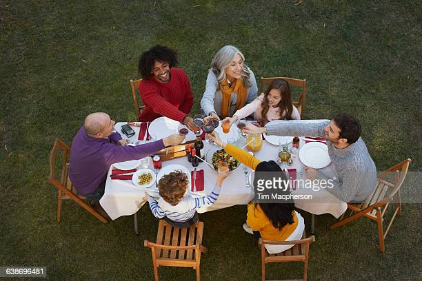 Overhead view of multi generation family dining outdoors, making a toast smiling
