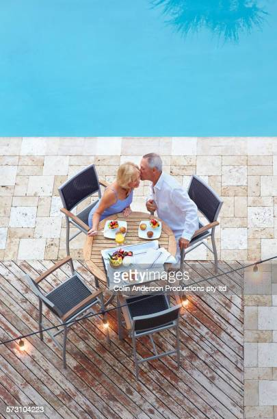 Overhead view of older Caucasian couple at table near swimming pool