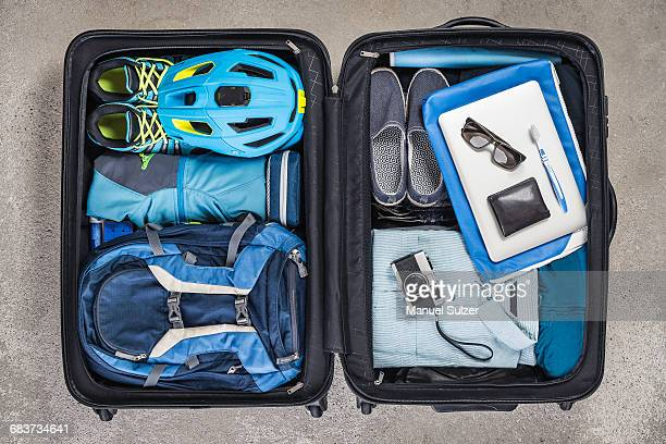 Overhead view of open packed suitcase with blue shirt, bike helmet, backpack, retro camera and toothbrush