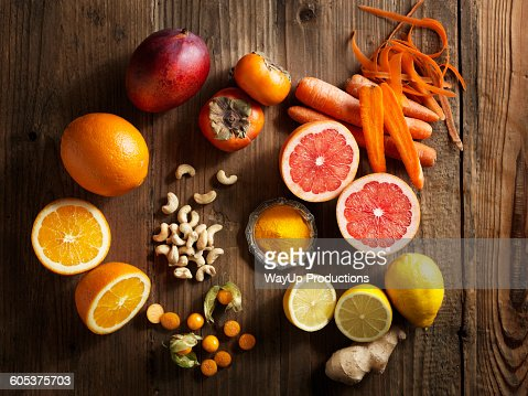 Overhead view of orange fruit and vegetables on wood grain pattern background : Stock Photo