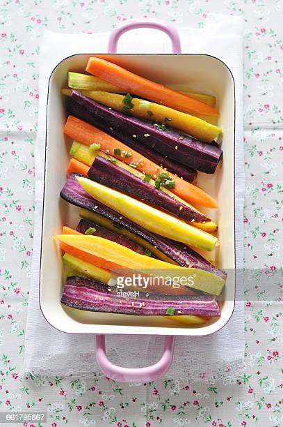 Overhead view of orange, purple and yellow carrots in baking dish