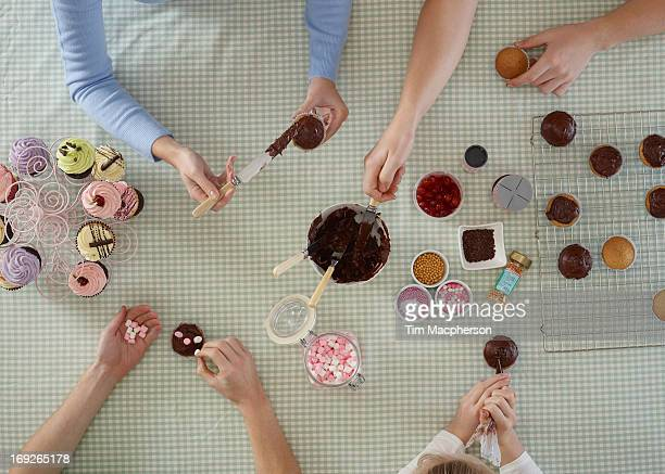 Overhead view of people decorating cakes