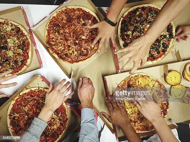 Overhead View Of People Having Pizzas At Table