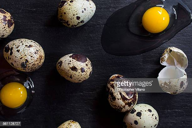 Overhead view of quail eggs and cracked shell with raw eggs