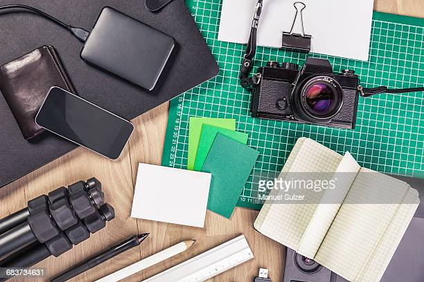 Overhead view of retro camera, notebook, diary, external hard drive, wallet, tripod and smartphone