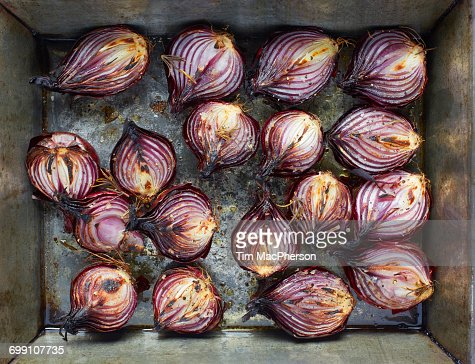 Overhead view of roasted red onion halves with rosemary and olive oil in roasting tin