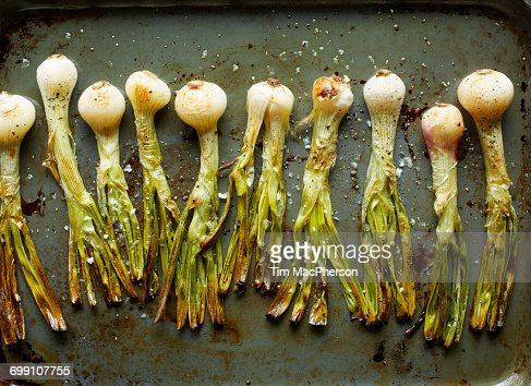 Overhead view of roasted whole spring onions in roasting tin