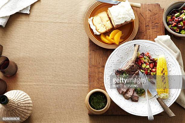 Overhead view of South American dinner with plate of steak, corn, kidney bean salad and salsa verde