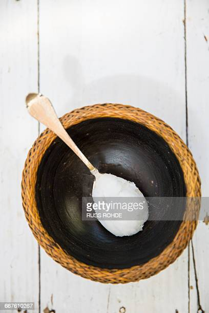 Overhead view of spoonful of cold coconut oil on bowl