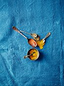 Overhead view of spoonfuls of turmeric and paprika spices on blue background
