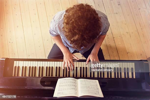 オーバヘッドの 10 代の少年ピアノの鍵盤で日光ルーム