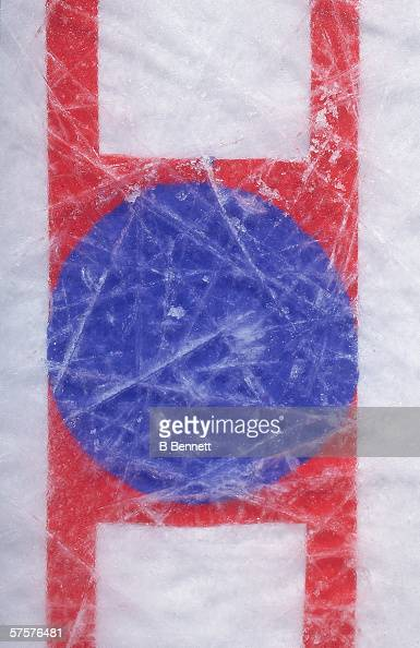 Overhead view of the faceoff circle in the center of an ice hockey rink shows the scratches of use late 20th Century